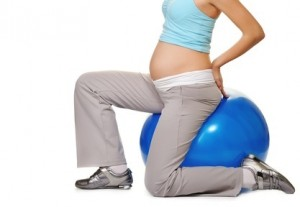 pregnant woman making exercise on a fitness ball